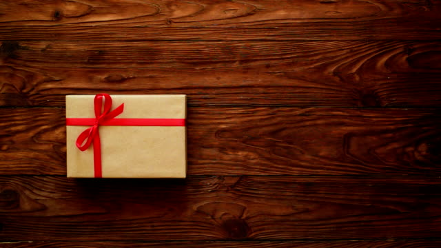 hands putting a gift box on table and adding a greeting card in a form on heart - table top view stock videos & royalty-free footage