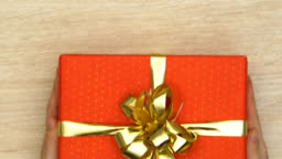 Hands putting gift box on table, present for beloved one, holiday celebration
