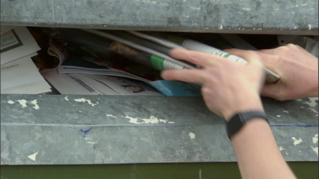 zi, cu, hands putting newspapers into recycling bin, ardley, oxfordshire, united kingdom - giornale video stock e b–roll