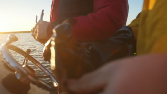 hands putting on gloves in boat on lake - schiffsdeck stock-videos und b-roll-filmmaterial