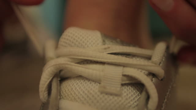 hands reach down to tie a white tennis shoe - tied up stock videos & royalty-free footage