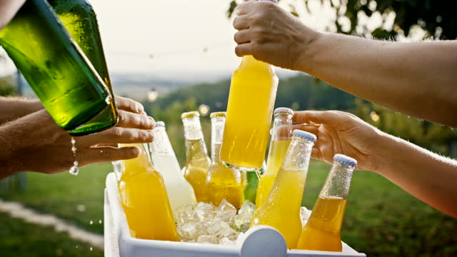 slo mo hands reaching for bottles of cold drink while having a garden party - cold drink stock videos & royalty-free footage