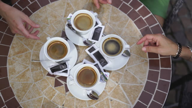 hands reaching for cups of espresso on coffee table - coffee table stock videos & royalty-free footage