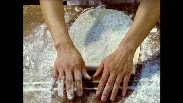 stockvideo's en b-roll-footage met hands rolling bread dough on a floured surface; 1989 - breedbeeldformaat