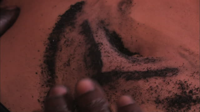 hands rub soot over patterned wounds, creating a dark, tattooed  scar. - soot stock videos & royalty-free footage