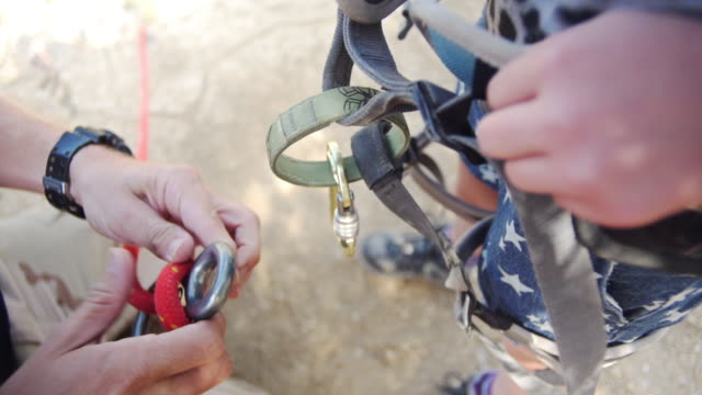 hands securing carabiner on climbing harness - imbracatura di sicurezza video stock e b–roll