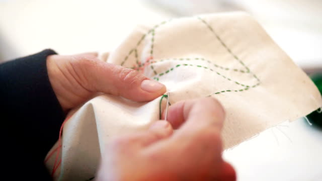 hands sewing fabric with needle. - craft product stock videos and b-roll footage