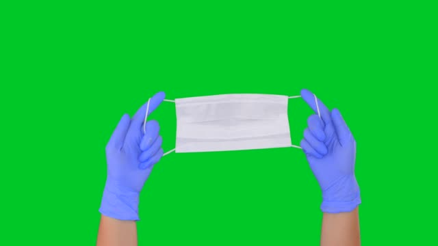hands showing a protective face mask on chroma key green screen - glove box stock videos & royalty-free footage