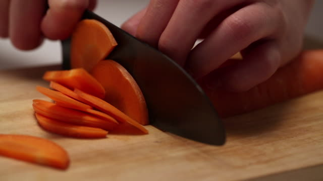 ECU R/F TS Hands slicing Carrot with knife on cutting board / Seoul, South Korea