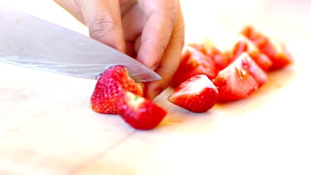 stockvideo's en b-roll-footage met handen moten verse aardbeien op houten snijplank. - vitamine c