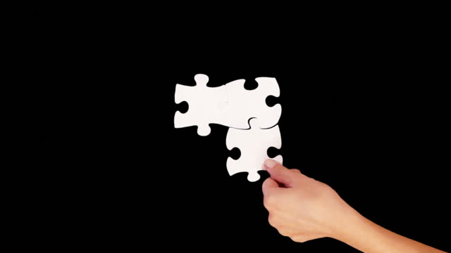 hands solving a puzzle. black background. luma matte. - puzzle stock videos and b-roll footage