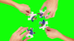 Hands solving a puzzle. Green Screen and Wood. Earth.
