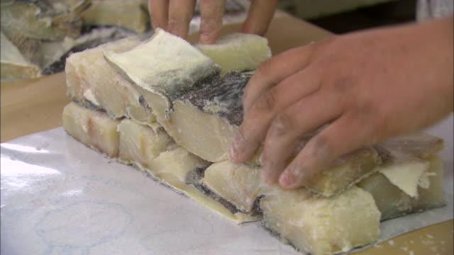 hands stacking blocks of salted cods - タラ点の映像素材/bロール