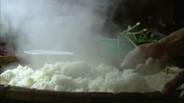 cu hands stirring steaming rice, laos - 蒸気点の映像素材/bロール