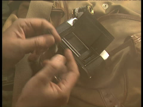 Hands take apart camera and insert film into it