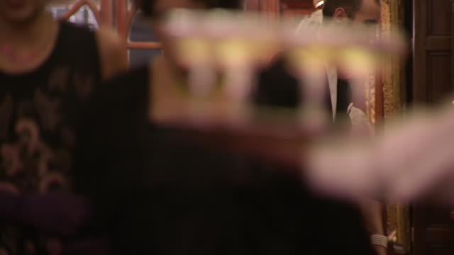 ms r/f hands taking glasses of champagne from tray / london, united kingdom - 盆点の映像素材/bロール