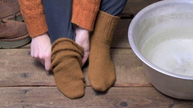 Mains qui décollait des chaussettes de laine