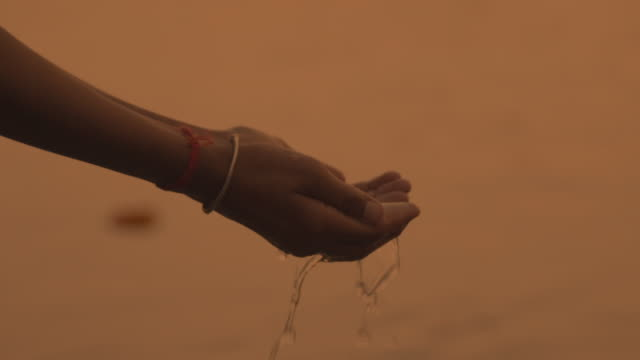 C/U hands taking water of the Ganges river