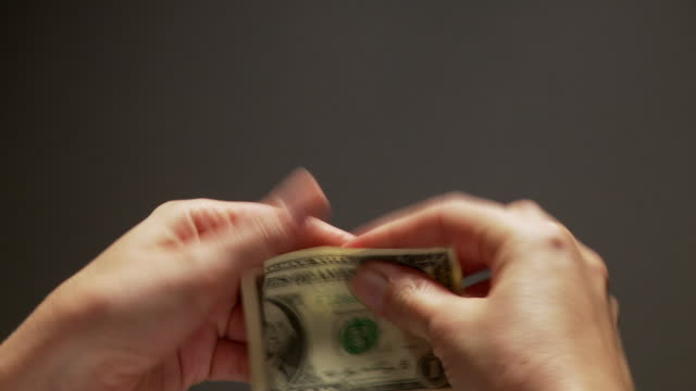 CU Hands tearing up U.S. dollar bill into small pieces