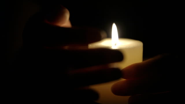 hands that protect the flame of a candle - candlelight stock videos & royalty-free footage