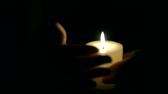 vídeos de stock e filmes b-roll de hands that protect the flame of a candle - memorial