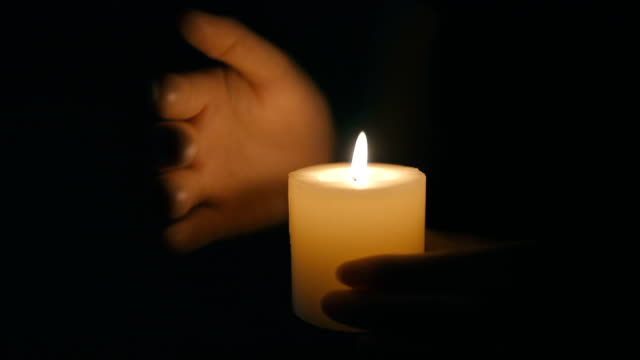 hands that protect the flame of a candle - candlelight stock videos and b-roll footage