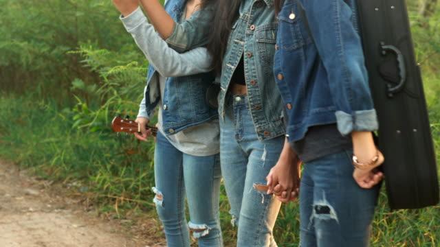 Die drei Mädchen halten Hände und gehen gemeinsam im Wald