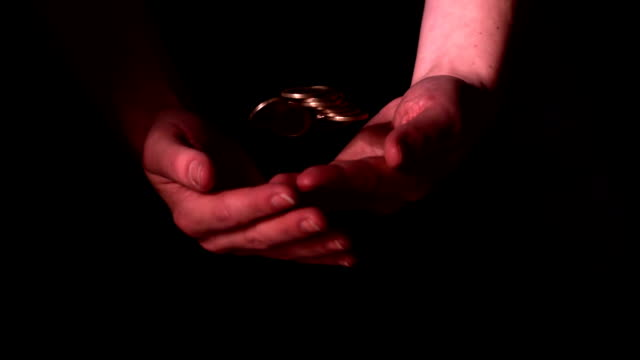 hands throwing coins and catching them on black background - money makes the world go around stock videos and b-roll footage