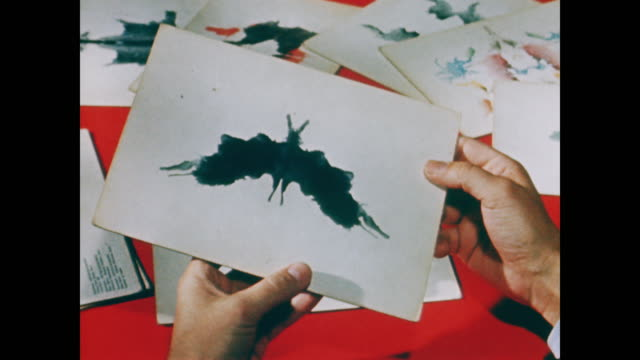 vídeos de stock, filmes e b-roll de hands turn a rorschach ink blot around before figurative sketches are laid out on a table - 1958