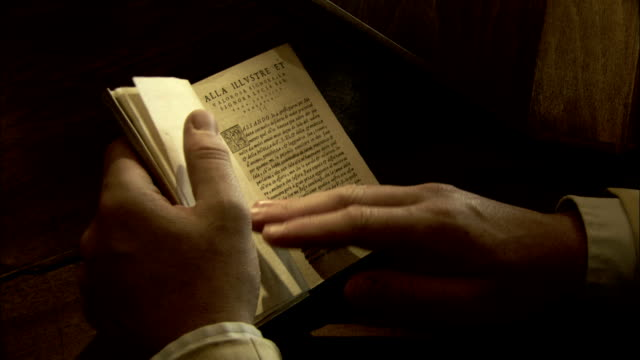 Hands turn the pages of a small book. Available in HD.