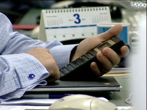 Hands type numbers on calculator keypad in office fingers drumming on desk