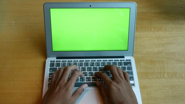 stockvideo's en b-roll-footage met handen typen laptop notebook met groen scherm op houten bureau achtergrond, 4k(uhd) - diavoorstelling