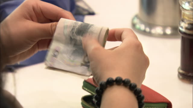 cu hands unfold yuan notes in a restaurant, china - paying stock videos & royalty-free footage