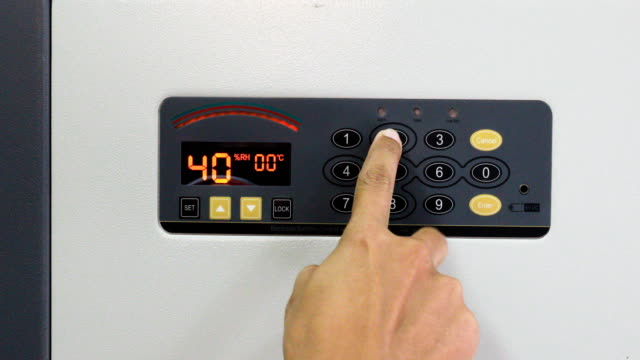 Hands unlocking combination to open safe box