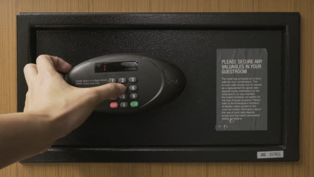Hands unlocking combination to safe in the hotel room
