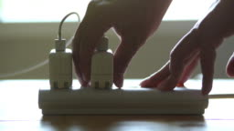 Hands unplug many adaptor from the electrical outlet and turn off the electricity switch on the table