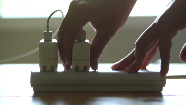 hands unplug many adaptor from the electrical outlet and turn off the electricity switch on the table - electrical component stock videos & royalty-free footage
