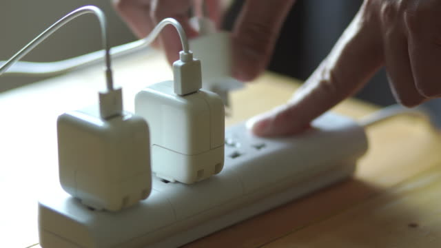 hands unplug many adaptor from the electrical outlet and turn off the electricity switch on the table - plug socket stock videos & royalty-free footage