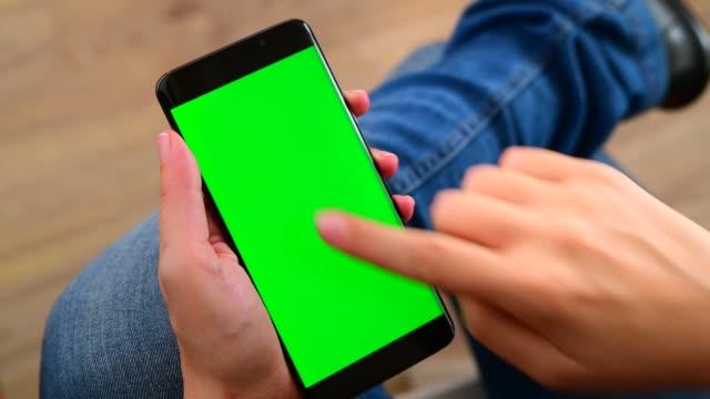 vídeos y material grabado en eventos de stock de manos usando un teléfono inteligente con pantalla de croma - deslizar
