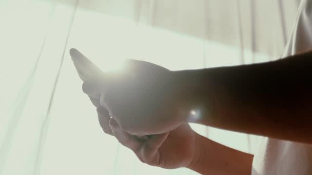 vídeos de stock, filmes e b-roll de mãos usando um smartphone - reflexo efeito de luz