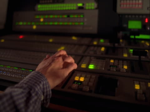 Hands using controls in TV control room