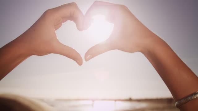 vídeos de stock, filmes e b-roll de as mãos - símbolo do coração