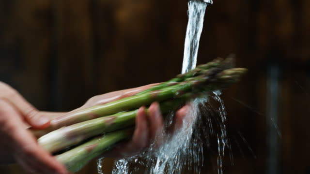 hands washing asparagus
