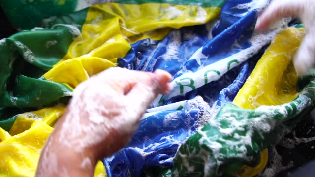 hands washing brazilian flag - new brazil/corruption concept - corruption stock videos and b-roll footage