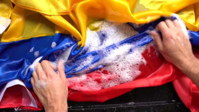 hands washing colombian flag - change colombia/corruption concept - colombian flag stock videos and b-roll footage