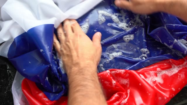 hands washing russian flag - change russia/corruption concept - russian culture stock videos & royalty-free footage