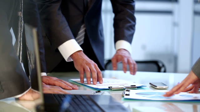 Hands with business documents at meeting