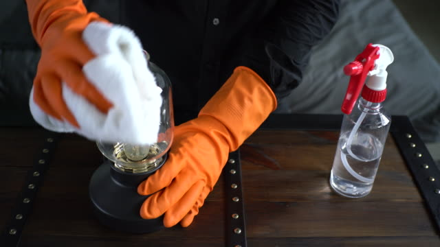 hands with protective glove disinfecting small lamp - washing up glove stock videos & royalty-free footage