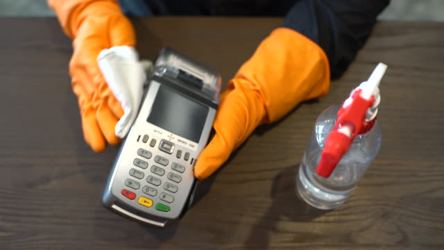 hands with protective gloves disinfecting credit card reader - credit card reader stock videos & royalty-free footage
