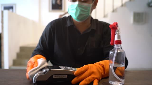 vídeos y material grabado en eventos de stock de hands with protective gloves disinfecting credit card reader - asia sudoriental